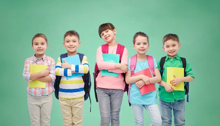 children school: childhood, preschool education, learning and people concept - group of happy smiling little children with school bags and notebooks over green chalk board background