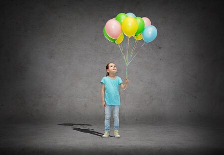 girl looking up: childhood, fashion, imagination and people concept - happy little girl looking up and holding bunch of colorful helium balloons on strand over concrete room background