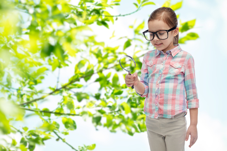 descubridor: la infancia, el medio ambiente, la ecología, el descubrimiento y el concepto de la gente - niña feliz en gafas con lupa sobre fondo verde natural Foto de archivo