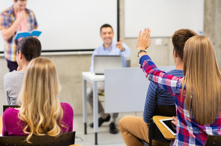 raising: education, high school, teamwork and people concept - group of students raising hand and teacher in lecture hall or classroom