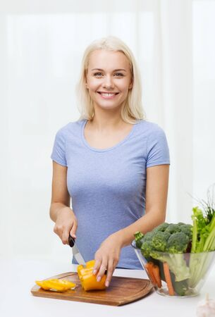 cocina saludable: healthy eating, vegetarian food, cooking, dieting and people concept - smiling young woman chopping vegetables at home