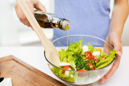 gezond eten, vegetarisch voedsel, het op dieet zijn en mensenconcept - sluit omhoog van jonge vrouw die plantaardige salade met olijfolie thuis kleden Stockfoto