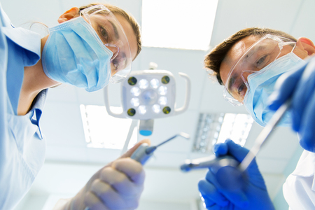 treating: people, medicine, stomatology and health care concept - close up of dentist and assistant with dental mirror, drill and air water gun spray treating patient teeth at dental clinic Stock Photo