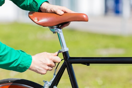 clavados: people, vehicle, eisure and lifestyle - close up of man adjusting fixed gear bike saddle high Foto de archivo