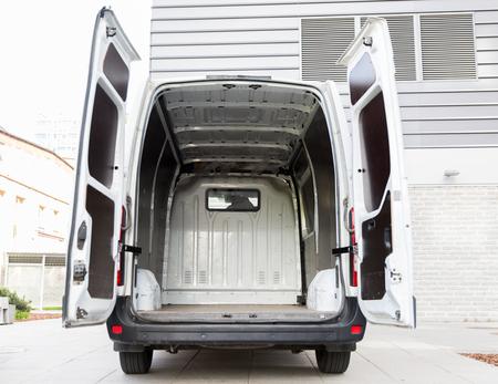 Gütertransport, Logistik, Transport und Fahrzeugkonzept - weiße leere Minivan Auto mit offenen Türen auf Stadt Parkplatz
