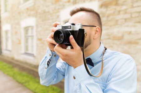 taking photograph: people, photography, technology, leisure and lifestyle - close up of young hipster man with retro vintage film camera on city street Stock Photo