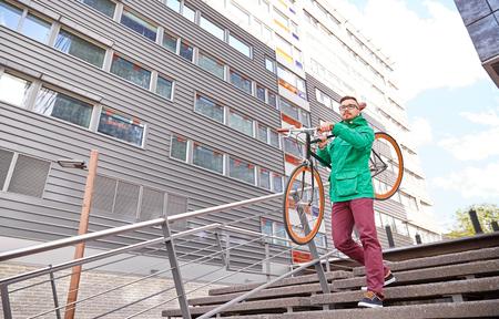 bajando escaleras: la gente, el deporte, el estilo, el ocio y estilo de vida - hombre joven que lleva inconformista bicicleta fija del engranaje en el hombro por las escaleras en la ciudad