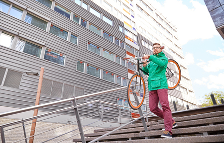 shoulder carrying: people, sport, style, leisure and lifestyle - young hipster man carrying fixed gear bike on shoulder down stairs in city Stock Photo