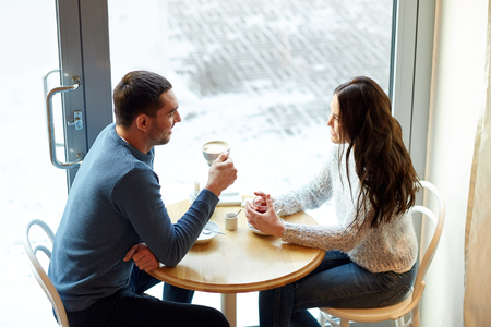 young happy couple: people, communication and dating concept - happy couple drinking tea and coffee at cafe