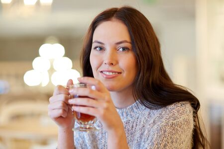 tea table: leisure, drinks, people and lifestyle concept - smiling young woman drinking tea at cafe Stock Photo