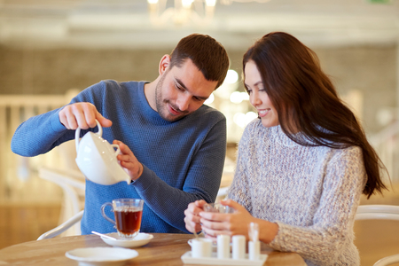 tea table: people, communication and dating concept - happy couple drinking tea at cafe or restaurant