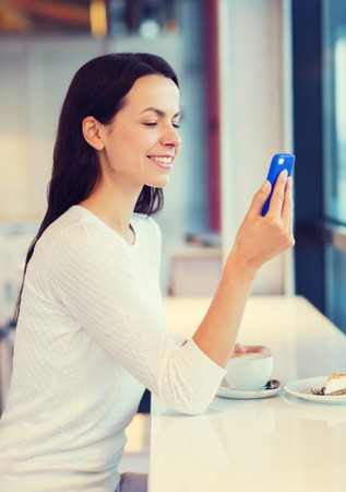 hispanic woman: drinks, food, people, technology and lifestyle concept - smiling young woman with smartphone drinking coffee at cafe
