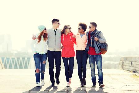personas reunidas: el turismo, los viajes, la gente y el concepto de la amistad - grupo de amigos adolescentes felices que recorren a lo largo de calle de la ciudad y que hablan Foto de archivo