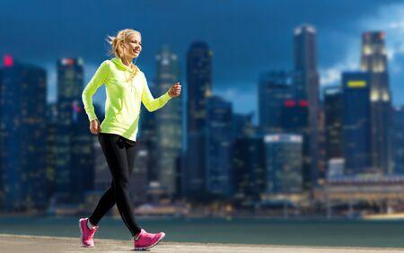 ropa deportiva: gimnasio, el deporte, la gente y el concepto de estilo de vida saludable - mujer feliz trotar sobre calle de la ciudad de fondo