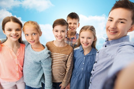youth group: childhood, friendship, technology and people concept - happy children talking selfie over blue sky and clouds background