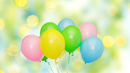 blue and green: holidays, birthday, party and decoration concept - bunch of inflated colorful helium balloons over green summer lights background