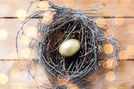 Twigs: easter, holidays, tradition and object concept - close up of golden easter egg in nest on wooden surface over holidays lights Stock Photo