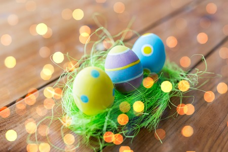 artificial lights: easter, holidays, tradition and object concept - close up of colored easter eggs and decorative grass on wooden surface over holidays lights Stock Photo