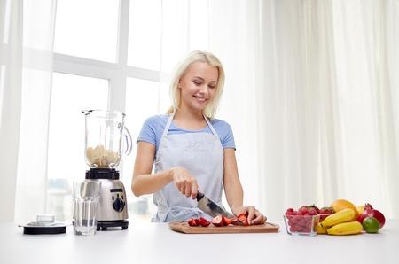 gezond eten, koken, vegetarisch eten, op dieet zijn en mensen concept - glimlachend jonge vrouw met blender hakken fruit en bessen voor fruit schudden thuis