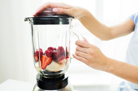 licuadora: alimentación saludable, cocinar, comida vegetariana, la dieta y el concepto de personas -cerca de la mujer con la licuadora hacer batido de frutas r en casa