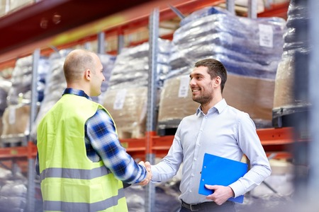 business partnership: wholesale, logistic, people and export concept - manual worker and businessmen with clipboard shaking hands and making deal at warehouse