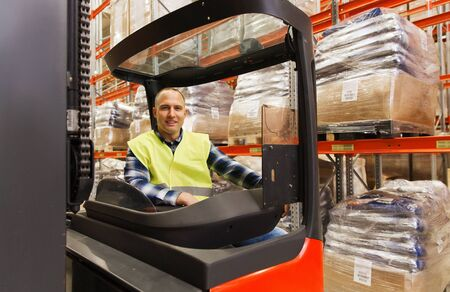 wholesale, logistic, loading, shipment and people concept - smiling man or loader operating forklift loader at warehouse Stock Photo