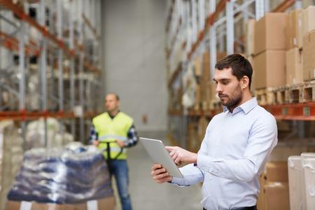al por mayor, logística, comercial, exportación y concepto de la gente - hombre o gerente con la comprobación de la tablilla del ordenador PC de las mercancías en el almacén