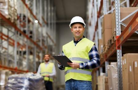 mayoristas, logística, personas y concepto de exportación - el hombre con el portapapeles en el chaleco reflectante de seguridad en el almacén Foto de archivo