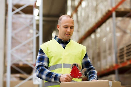 reflective: logistic, delivery, shipment, people and export concept - happy man in safety vest packing box or parcel with   tape at warehouse or mail storage Stock Photo