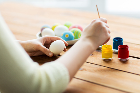 advertising design: easter, holidays, tradition and people concept - close up of woman coloring easter eggs with colors and brush