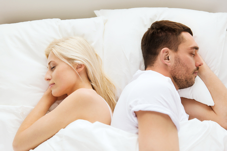 bedtime: people, rest, bedtime and family concept - couple sleeping back to back in bed at home