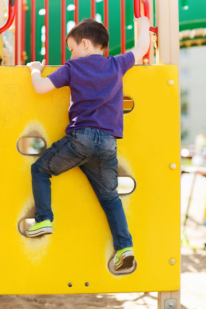 climbing frame: summer, childhood, leisure and people concept - happy little boy on children playground climbing frame from back Stock Photo