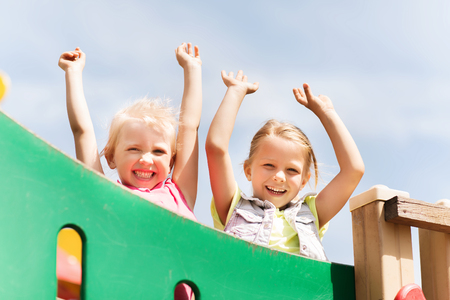 summer, childhood, leisure, friendship and people concept - happy little girls waving hands on children playground climbing frame Stock Photo