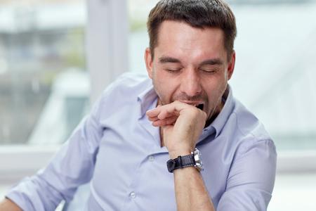 cansancio: la gente y el concepto de cansancio - Hombre cansado que bosteza en su casa u oficina Foto de archivo