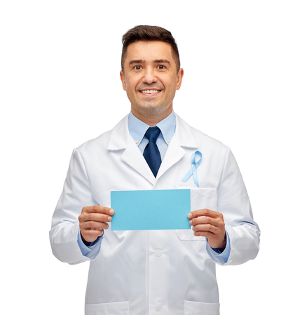 oncologist: healthcare, advertisement, people and medicine concept - smiling male doctor in white coat with sky blue prostate cancer awareness ribbon holding blank paper