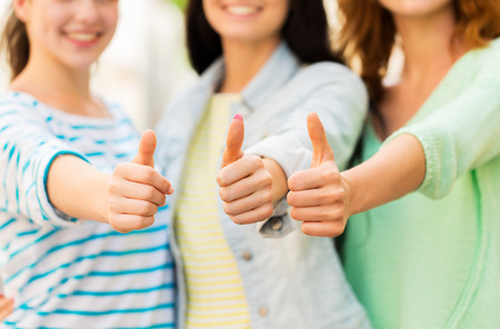 women friendship: vacation, leisure and friendship concept - close up of happy young women showing thumbs Stock Photo