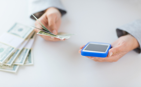 money business: business, finance, saving, technology and people concept - close up of woman hands with smartphone and us dollar money