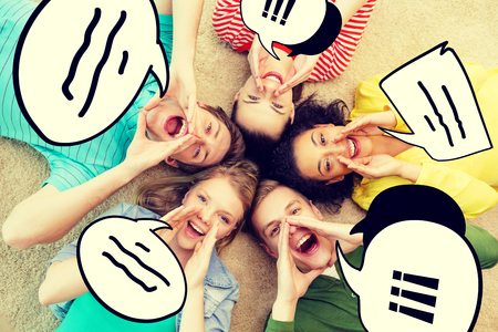 friendship, lifestyle and happiness concept - group of young smiling people lying on floor in circle screaming and shouting