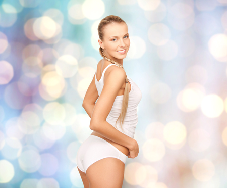 beautiful woman body: people, beauty, body care and fashion concept - happy beautiful young woman in cotton underwear over blue holidays lights background