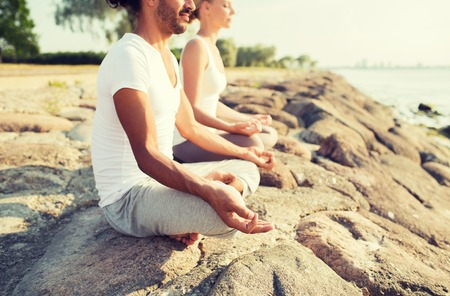 team lotus: fitness, sport, people and lifestyle concept - close up of couple making yoga exercises sitting on pier outdoors