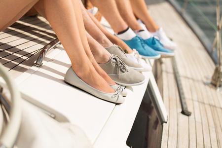 piernas mujer: vacaciones, viaje, mar, la vela y el concepto de la gente - cerca de amigos piernas sentado en la cubierta del yate Foto de archivo