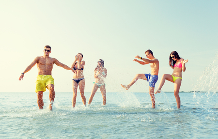 youth group: friendship, sea, summer vacation, holidays and people concept - group of happy friends having fun on beach