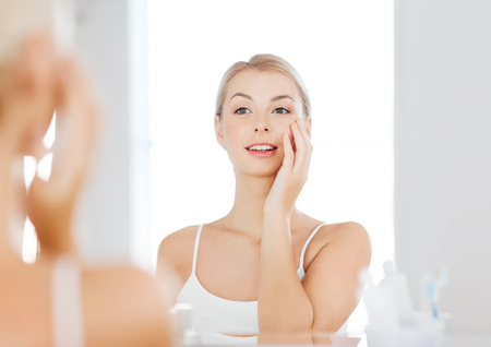 girl  care: beauty, hygiene, morning and people concept - smiling young woman looking to mirror at home bathroom