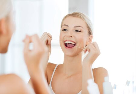 health care, dental hygiene, people and beauty concept - smiling young woman with floss cleaning teeth and looking to mirror at home bathroom