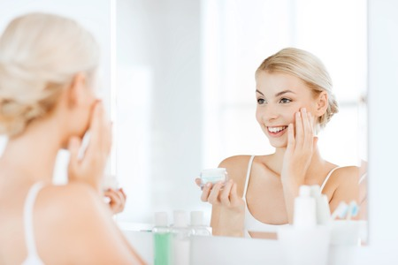 woman face cream: beauty, skin care and people concept - smiling young woman applying cream to face and looking to mirror at home bathroom