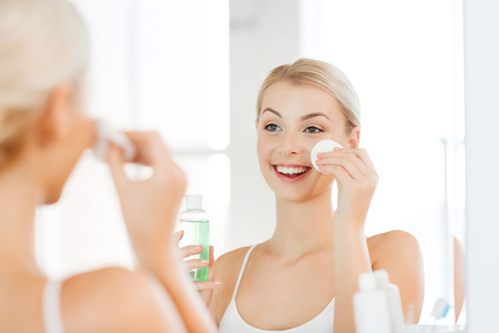 facial: beauty, skin care and people concept - smiling young woman applying lotion to cotton disc for washing her face at bathroom