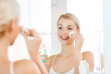 masajes faciales: belleza, cuidado de la piel y el concepto de la gente - sonriente mujer joven de aplicar la loción en un disco de algodón para lavar su cara en el baño Foto de archivo