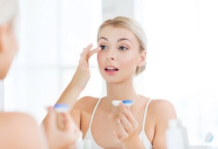 beauty, vision, eyesight, ophthalmology and people concept - young woman putting on contact lenses at mirror in home bathroom Stock Photo
