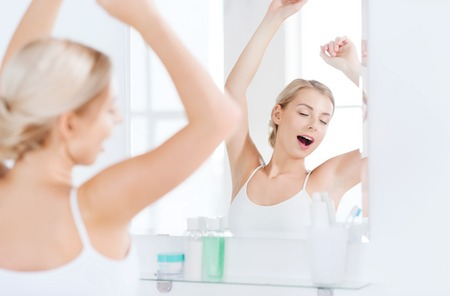 wakening: morning, awakening, morning and people concept - sleepy young woman yawning and stretching in front of mirror at bathroom Stock Photo