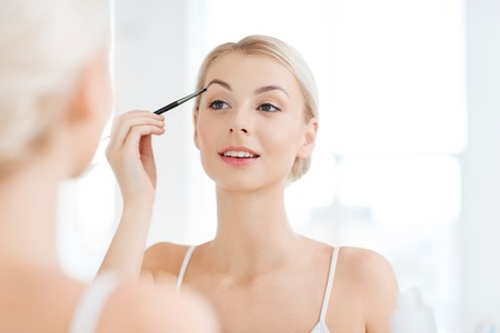 beauty, make up, cosmetics, morning and people concept - young woman applying makeup drawing eyebrow with brush and looking to mirror at home bathroom